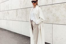 a white top, off-white pants, white trainers, a creamy coat for a chic neutral fall look