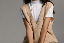 a white turtleneck, a tan knit vest, olive green pants for a casual fall outfit