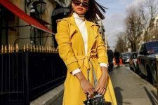 a white turtleneck, blue jeans, a sunny yellow trench and a black and yellow bag for the fall
