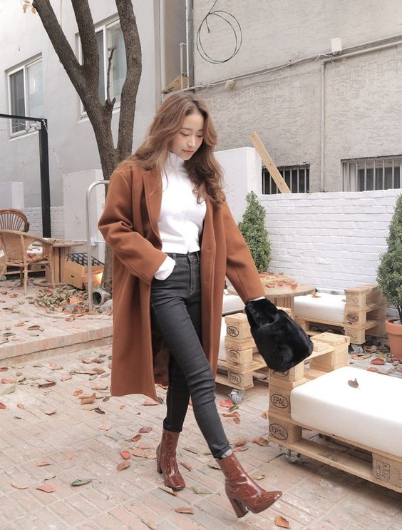 a white turtleneck, graphite grey jeans, brown booties, a brown coat and a bag