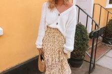 a yellow floral ruffle midi skirt, a white cardigan tucked in, white mules and a basket bag for a summer to fall look
