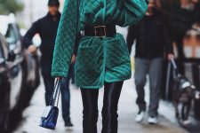 an emerald velvet quilted jacket with black buttons, a high neckline and a wide leather belt to accent the waist