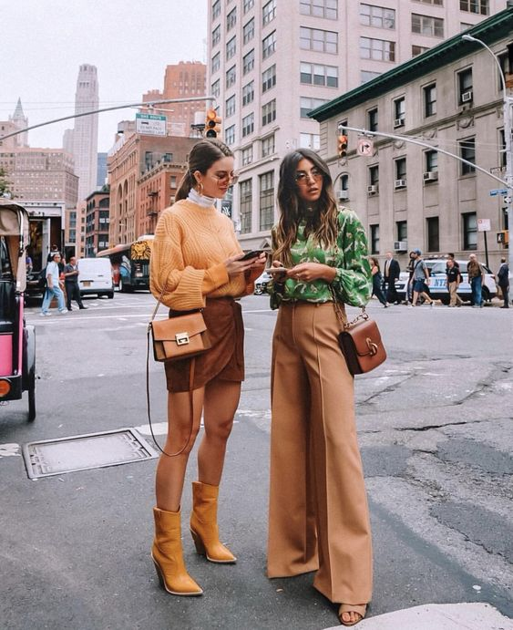 an orange sweater, a brown wrap mini, yellow boots, a white turtleneck and an amber bag