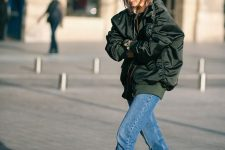 an oversized black bomber jacket, blue jeans, metallic booties for a stylish and bold fall outfit
