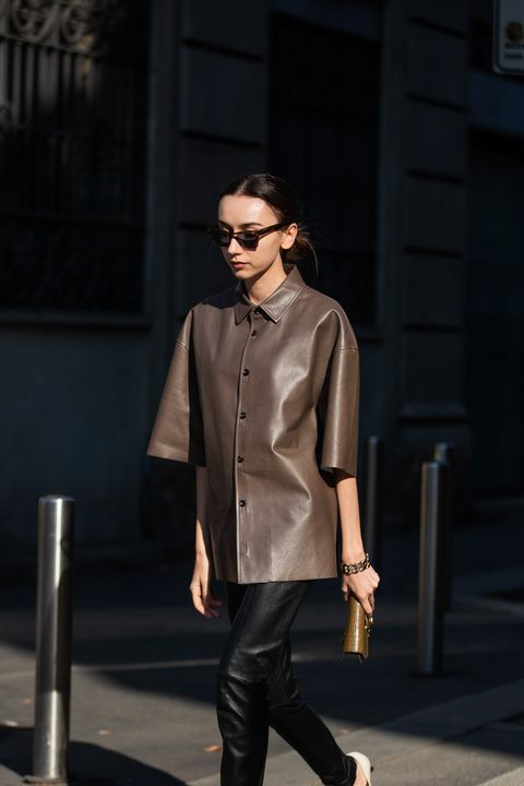 an oversized brown leather shirt, black leather pants, a small clutch and white shoes