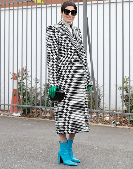 an oversized coat, a black clutch and bright accents - green gloves and bright blue ankle boots