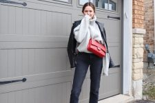 an oversized grey sweater, a black leather jacket, black straight leg jeans, white sneakers and a red bag