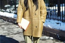 an oversized tan quilted jacket with pockets, green pants, a navy hat, an booties for a fall-infused look