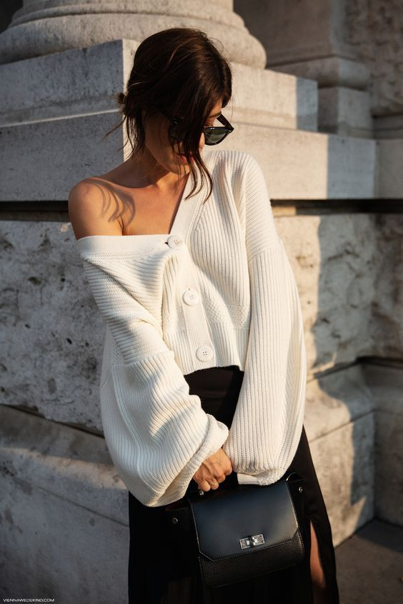 an oversized white cardigan tucked into a black A line skirt, a black bag for a day to night look