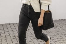 black denim, a white chunky knit cardigan, white shoes and a black bucket bag