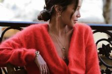 blue jeans, a red fluffy cardigan, layered necklaces and earrings for a bold and sexy fall look