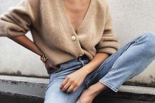 blue jeans, a tan fluffy cardigan worn as a shirt and matching mules for a casual work look
