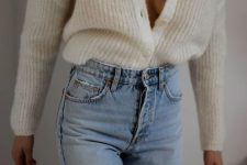 blue jeans paired with a white knit cardigan create a chic and relaxed look for the fall