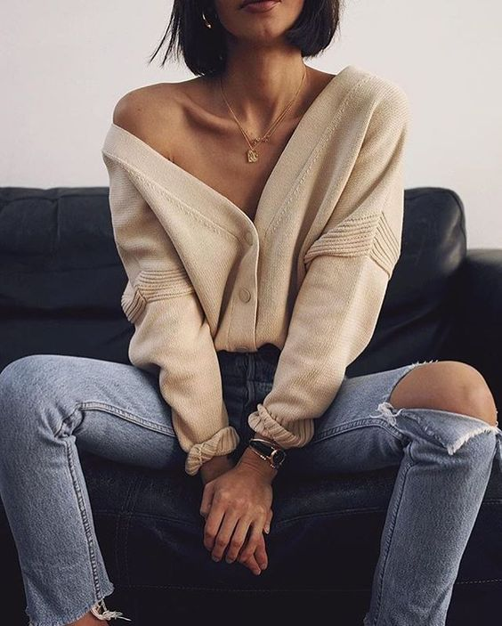 blue ripped jeans, a creamy cardigan tucked in, layered necklaces for a sexy look