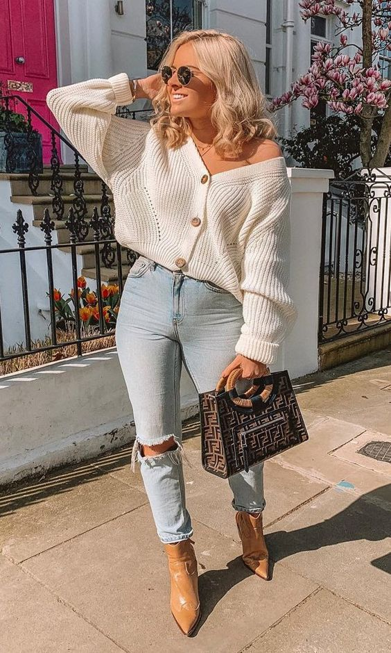 light blue ripped jeans, a creamy cardigan tucked in, tan booties and a printed bag for fall