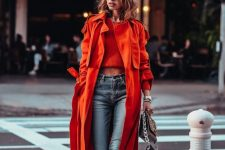02 a red crop top, blue jeans, black combat boots, a fiery red midi trench and a black bag