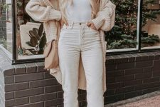 02 a white top, white jeans, tan booties, a chunky knit cardigan, a tan bag and a hat