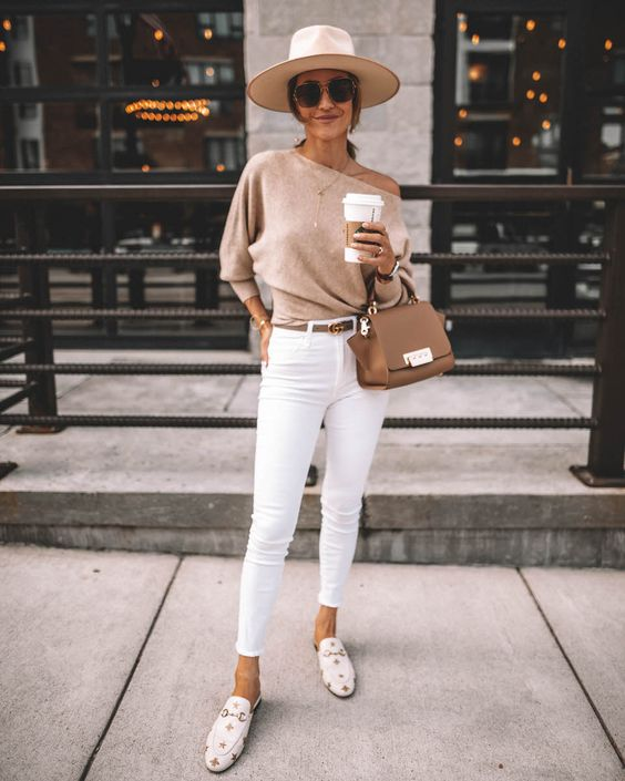 a tan one shoulder sweater, white skinnies, white printed mules, a hat and a brown bag