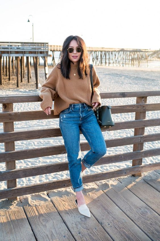 a tan ribbed sweater, blue jeans, white mules and a black bag for a stylish fall look