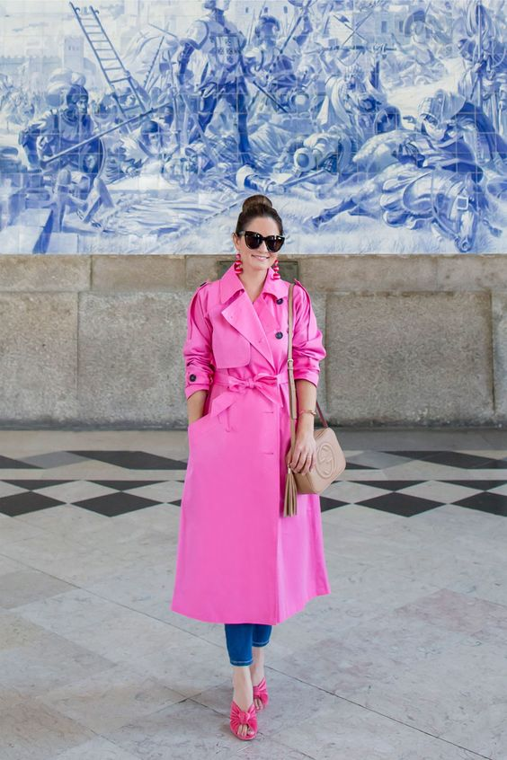 a hot pink trench, blue jeans, pink velvet mules and a tan bag for a bright fall look