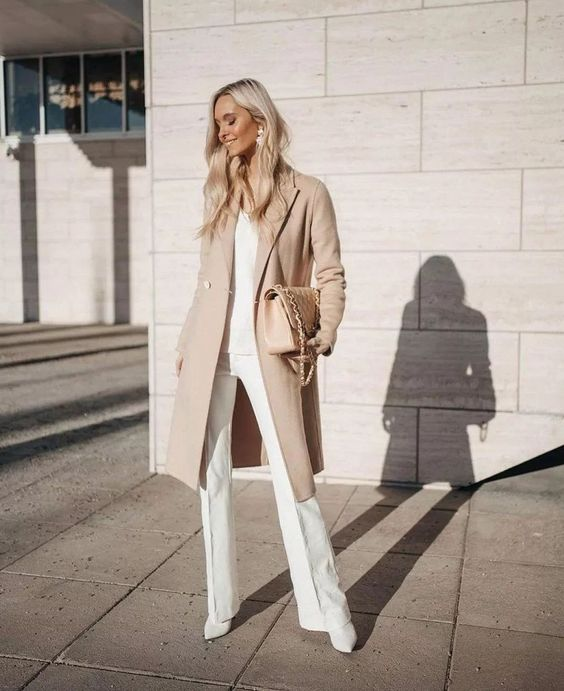 a chic neutral outfit with a white top and pants plus booties and a nude coat and a bag