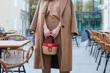 11 a stylish fall look with a brown top and pants, a camel coat, red heels and a wicker bag with a red part
