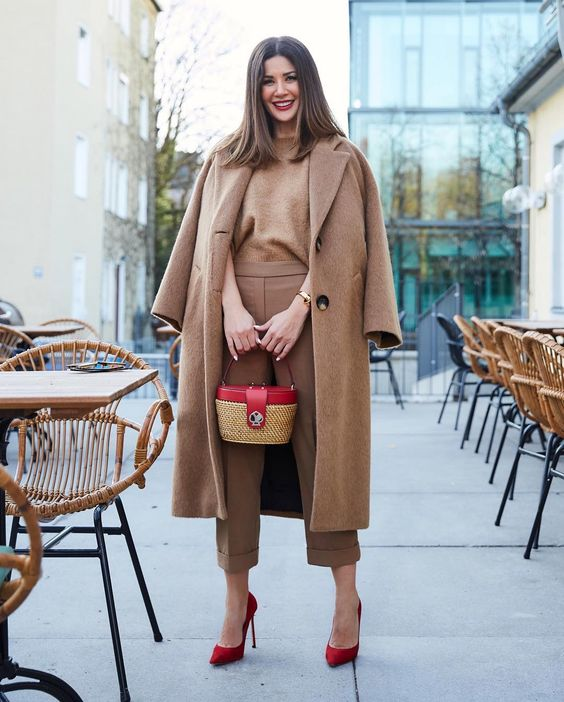a stylish fall look with a brown top and pants, a camel coat, red heels and a wicker bag with a red part