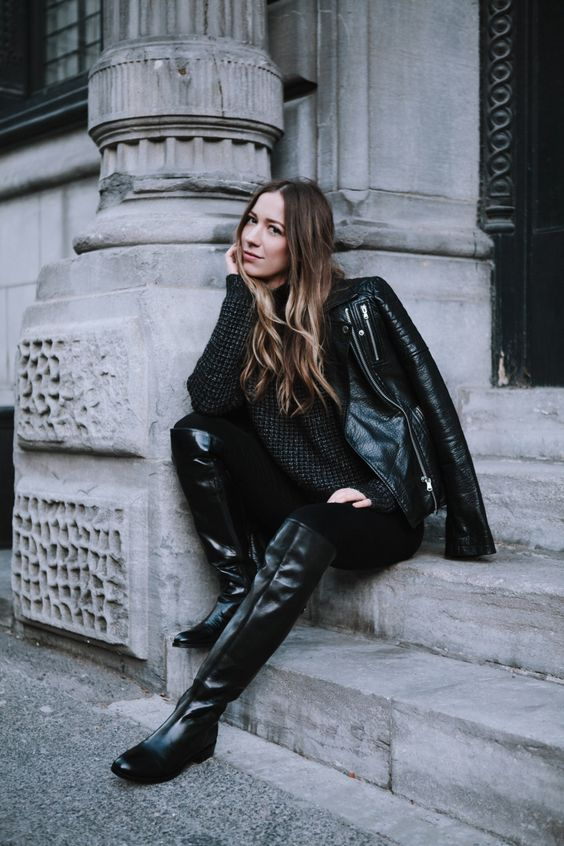 a total black look with a sweater, skinnies, riding boots, a black leather jacket