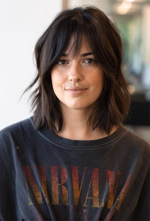 dark medium length hair with slight balayage and a shaggy long fringe is cool