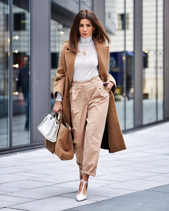 a white turtleneck, tan plaid pants, white cutout shoes, a camel coat, a came and white bag