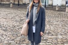 16 a simple and casual look with a white shirt, a grey sweater, grey pants, white trainers, a grey coat, a grye beanie and a tan bag