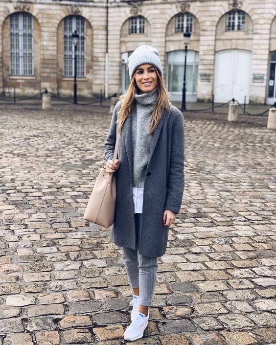 a simple and casual look with a white shirt, a grey sweater, grey pants, white trainers, a grey coat, a grye beanie and a tan bag