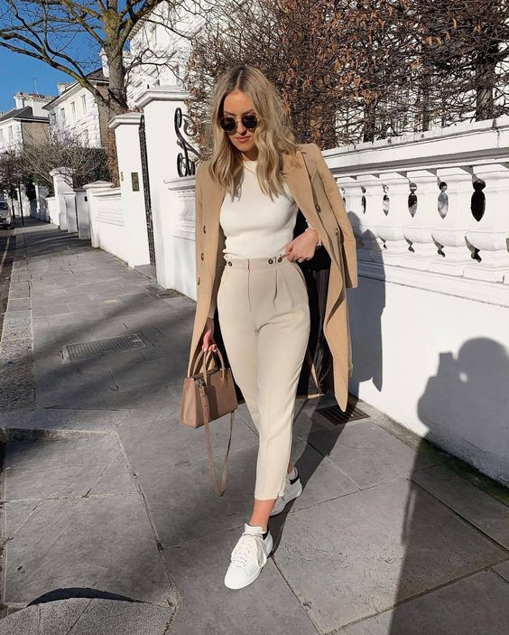 an elegant neutral work look with a white bodysuit, creamy pants, white sneakers, a tan bag and a camel coat
