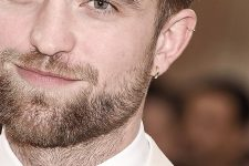 17 Robert Pattinson rocking a lobe and a helix piercing done with matching gold hoop earrings