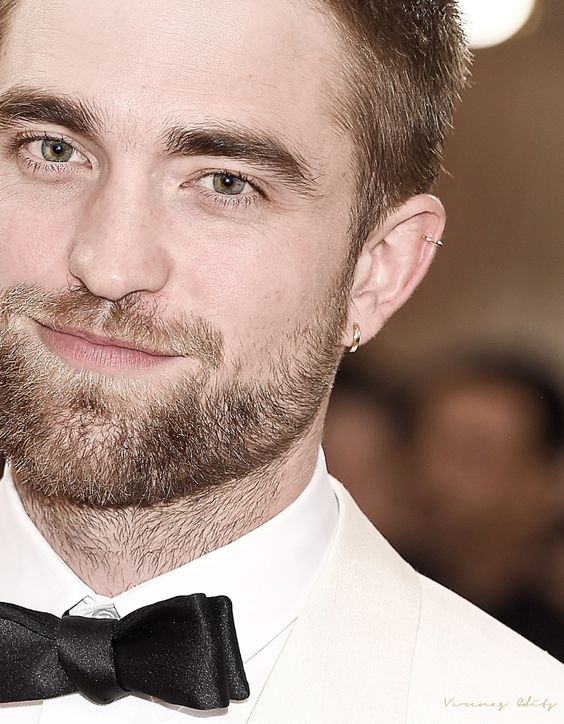 Robert Pattinson rocking a lobe and a helix piercing done with matching gold hoop earrings