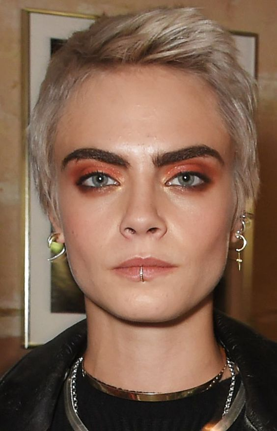 Cara Delevigne rocking several lobe piercings and a lip one done with a shiny rhinestone ring