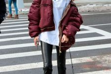Gigi Hadid wearing a black turtleneck, a white shirt, black leather pants, burgundy boots and a puffer jacket