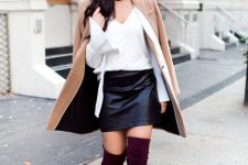 With V-neck shirt, black leather mini skirt and beige coat