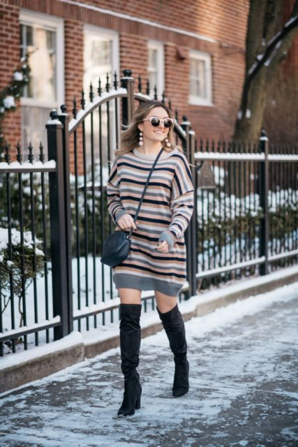 With black high boots and navy blue crossbody bag