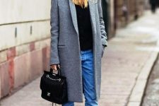 With black shirt, jeans, gray coat, black embellished bag and black lace up boots