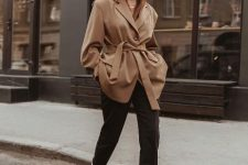 With black trousers, white mid calf boots and brown belted jacket
