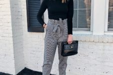 With black turtleneck, black leather clutch and white ankle boots