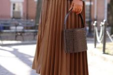 With brown gloves, brown pleated midi skirt, lace up shoes and leather bag