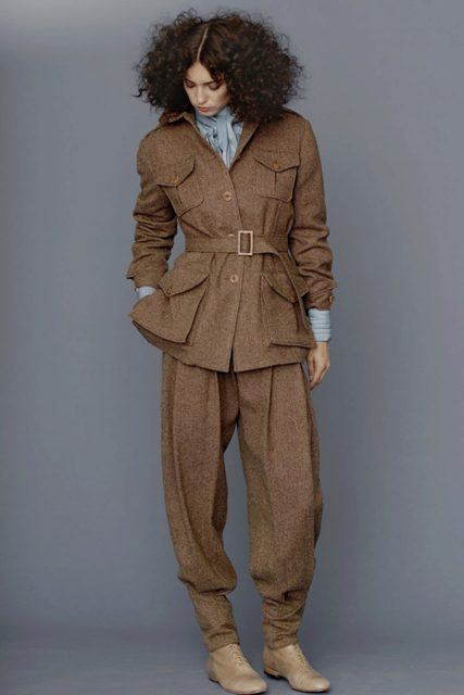With brown tweed trousers, light blue blouse and beige flat boots
