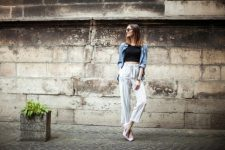 With denim jacket, black crop top, sunglasses and pale pink shoes