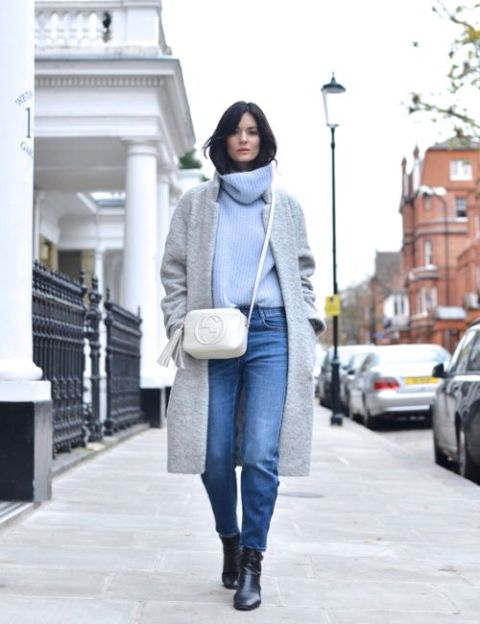 With gray coat, white bag, jeans and black boots
