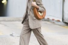 With gray printed suit, brown heeled boots and leather bag