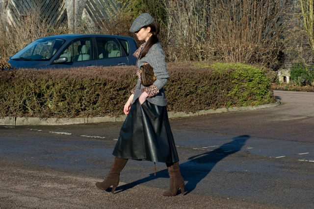 With gray sweater, brown suede boots and leather skirt