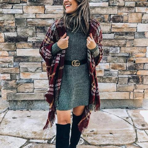With gray sweater dress, black belt and black high boots