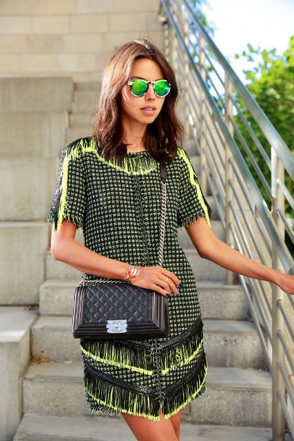 With mirrored sunglasses and black chain strap bag